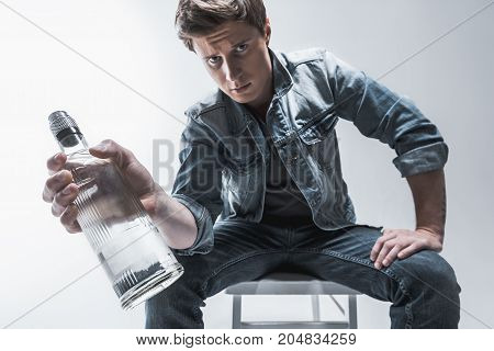 Do you really need this. Portrait of pensive man showing bottle of alcohol beverage to camera. He is sitting on chair. Low angle
