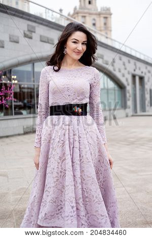 beautiful female in luxury dress standing outdoor in the city center