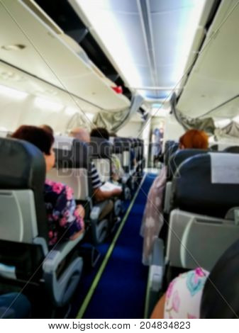 Blured view of the interior of modern commercial airplane with passengers on their seats waiting to taik off.