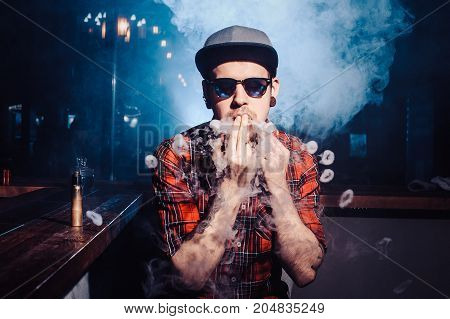 Punk Man In The Vape Shop Is Sitting At The Bar And Smoking A Mechanical Wipe Device