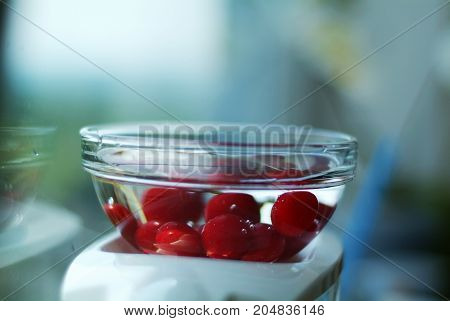 Freshly washed ripe cherries on the window on a cold autumn morning.