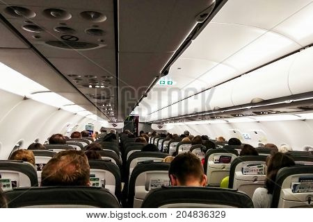 Prague Czech Republic - July 30 2017: Interior of modern commercial airplane with passengers on their seats waiting to take off