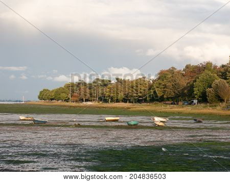 estuary scene in manningtree with moored boats tide clouds landscape