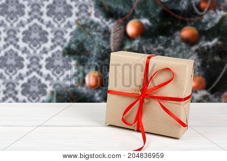 Christmas gift decorated with red ribbon on table, closeup, selective focus. Christmas tree background.