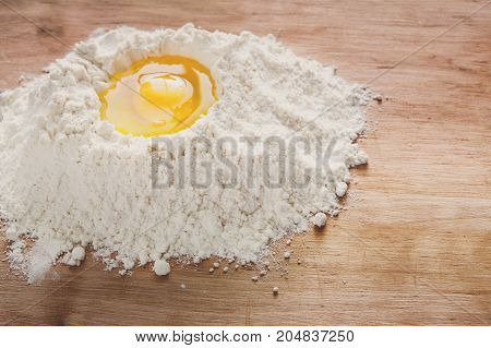 Baking concept. Flour and eggs on rustic wooden table, cooking ingredients. Making dough, copy space