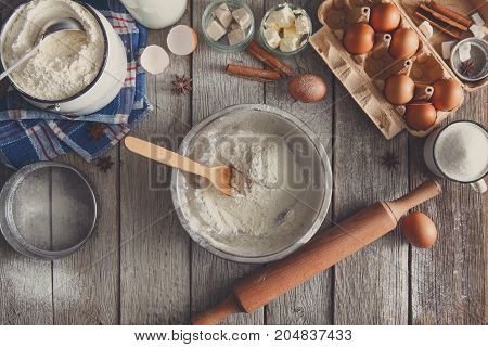 Baking background. Cooking ingredients for dough and pastry making on rustic wood.