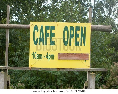a yellow sign close up cafe open 10am-4pm