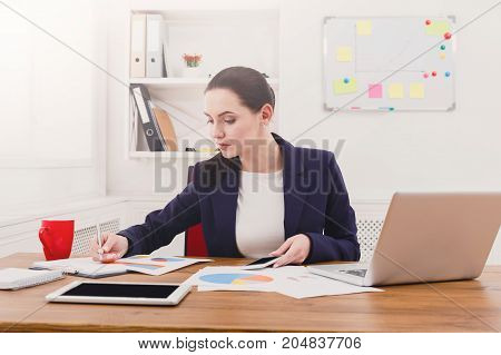 Paperwork in office. Concentrated female manager working on marketing strategy at workplace
