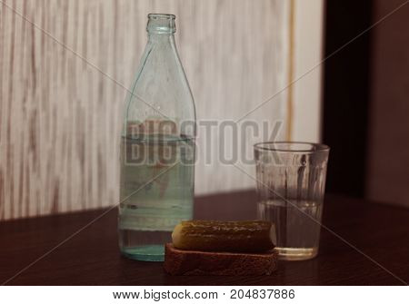 A retro composition consisting of a bottle of vodka a glass and a pickled cucumber with bread.
