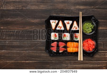 Japanese food delivery. Sushi and rolls top view with copy space on brown wood