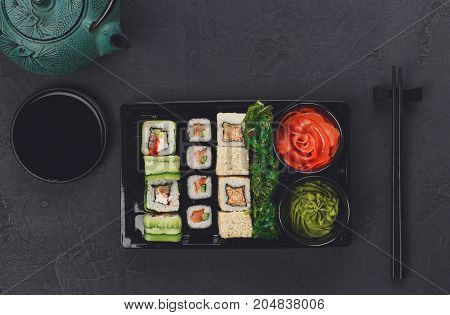 Japanese restaurant delivery, take away box top view, sushi maki and roll set. Chopsticks, ginger, soy sauce, wasabi and teapot. Meals at black background
