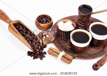 Coffee in copper coasters with accessories for coffee-drinking on a white background