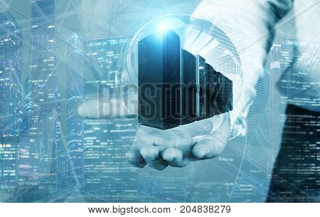 Businessman on blurred background holding a sphere hologram with servers in on the background of the business buildings
