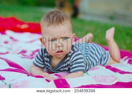 Newborn boy lying on the pink and white blankets on the green grass in the street and trying to keep head high