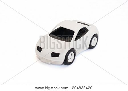 Plastic toy car is white with black wheels. Standing on a white background. Isolated.