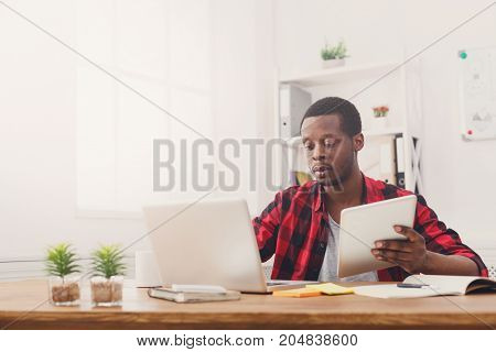 Serious young black businessman in office, work with laptop and tablet