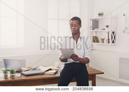 Serious african-american businessman in office, searching for new ideas on tablet