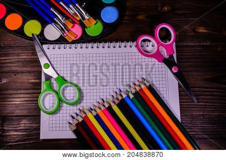 Set Of Different School Stationeries. Notepad, Scissors, Pensils, Paints, Paintbrushes On Wooden Des