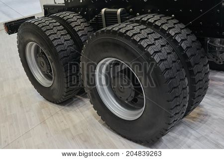 View on new truck wheels and tires on truck chassis. Truck wheel rim. Truck chassis parts details devices equipment. New wheels and tires on axles. Truck chassis