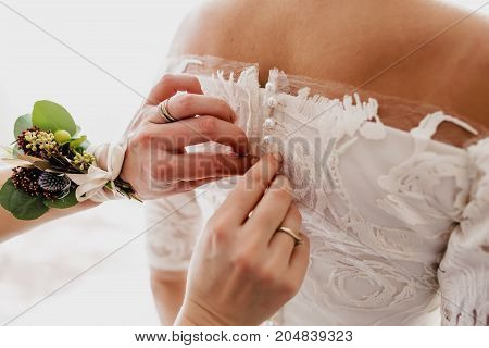 Mother helps fasten a wedding dress the bride before the ceremony. Wedding concept. Back view, close-up. Artwork