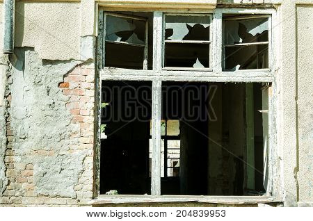 Demolished window of abandoned ruined house destroyed by grenade explosion in the war zone