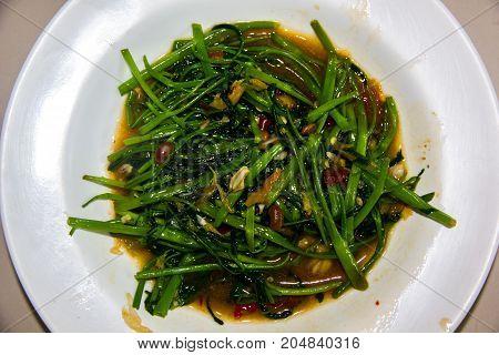 stir-fried morning glory thai food style on white dish