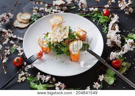 Restaurant dish on white plate on black background decorated with flowers served with fork and knife. Salad with spinach, arugula, cheese, salmon and baguette