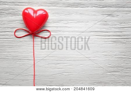 One candy heart for Valentine's Day with grey background.