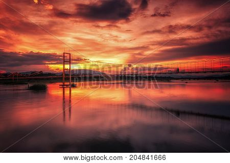 Landscape of sunset bridge crossing Ping river at Tak Thailand