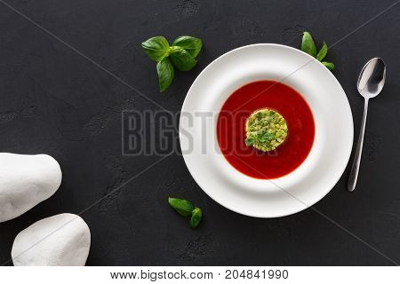 Delicious tasty cold tomato soup gazpacho with avocado top view. Portion of traditional Spanish red vegetable broth, restaurant serving with spoon, copy space