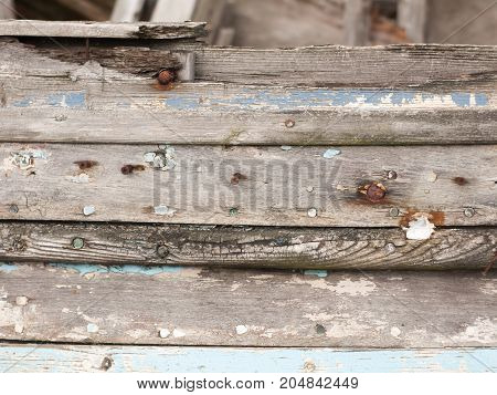 close up texture of decaying wooden boat with rusty nails