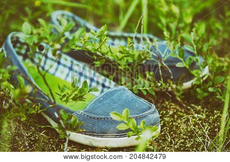 A pair of blue moccassin shoes in the green grass, fashion active footwear concept