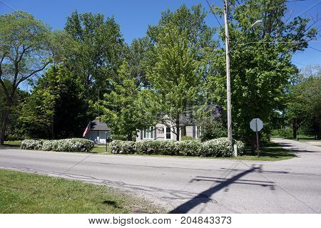 BAY VIEW, MICHIGAN / UNITED STATES - JUNE 13, 2017: A single family home, surrounded by shade trees and flowering bushes, on a corner in Bay View.
