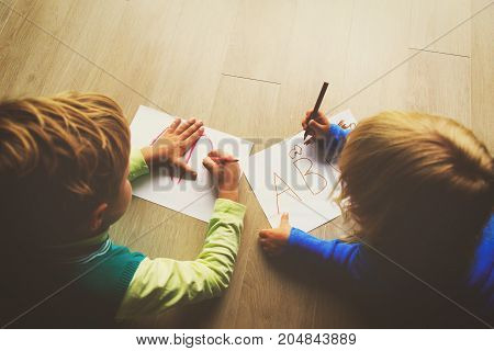 little boy and girl learn to write letters, do homework