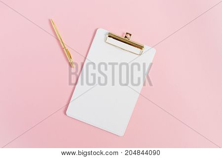 Minimal home office desk with clipboard and pen on pink background. Flat lay top view.