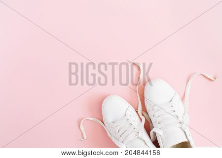 Fashion blog or magazine concept. White female sneakers on pink background. Flat lay top view minimal background.