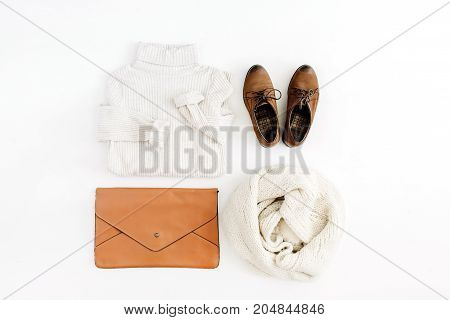 Women modern fashion clothes and accessories. Flat lay female casual style look with warm sweater shoes clutch and scarf. Top view.