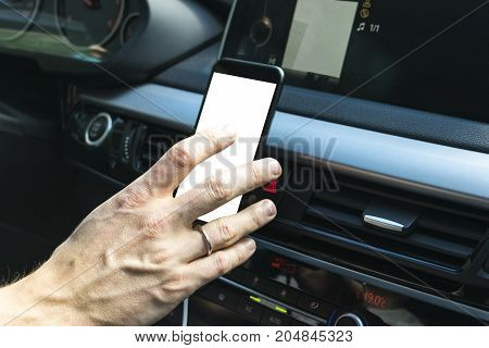 Male hand using smartphone in car. driving near the lake. Man driving a car inside cabin. Smartphone in holder with isolated white empty blank screen. Copy space