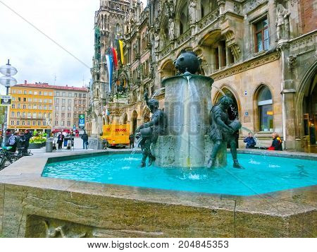 Munich, Germany - May 01, 2017: People near Fish Fountain with New Town Hall in the background at Marienplatz in Munich, Germany.