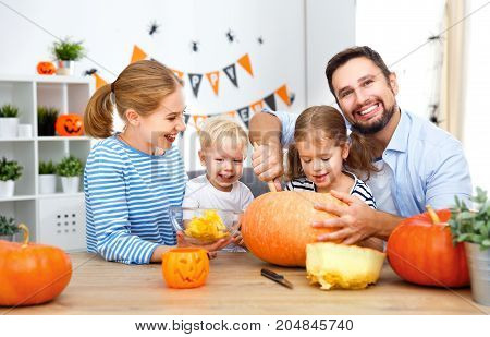 happy family mother father and children cut pumpkin for holiday of halloween