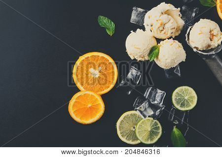 Ice cream scoops with ice cubes, lemon and orange slices, mint and scoop on black background. Delicious cold sweet dessert, top view, copy space
