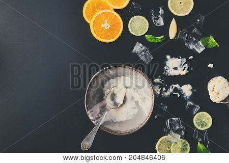 Empty bowl of ice cream with lemon and orange slices, ice cubes and mint on black background, messy dining place