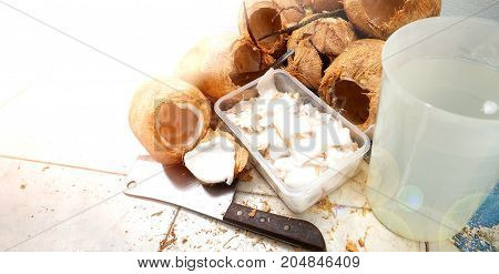 Peeled the Thai coconut for eat and drink has copy space The kitchen equipment has chopper knife spoon plastic box and jar on the floor.