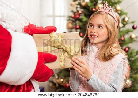 Portrait of excited girl receiving gift box from kind Santa Claus. She is laughing