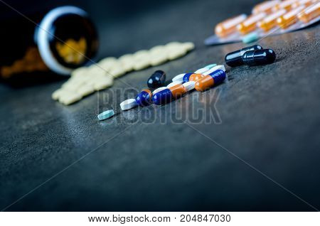 Medicines, supplements in a glass bottle. Pills spilling out from glass bottle. Medicine´s background. Pharmacy. Close up of capsules. Pack of tablets on a black background.