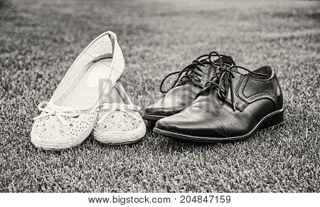 Women's and men's wedding shoes on the green grass. Symbol of love. Black and white photo.