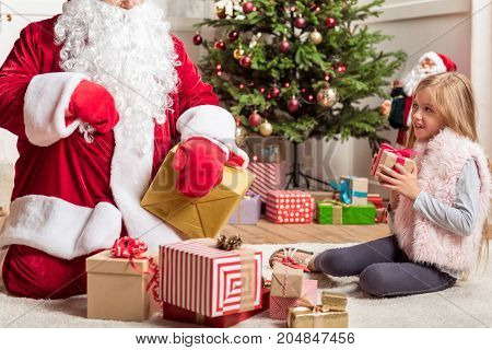 Are all these presents for me. Pretty girl is sitting near various gift boxes and looking at Santa Claus with curiosity. She is smiling