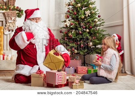 Give me one more present. Cute female child is looking at Santa Claus with hope. Fat man is sitting on floor and gesturing surprisingly