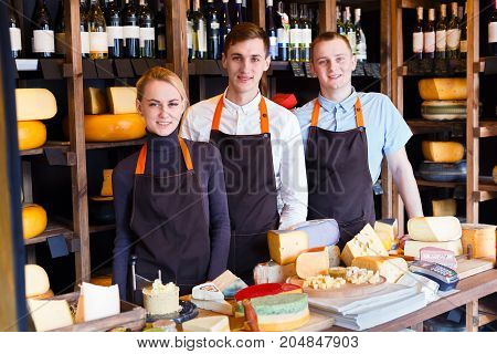 Cheese shop staff, sale clerks at counter waiting for clients. Male and female assistants