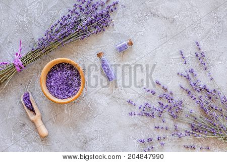 organic cosmetic set with lavender herbs and sea salt in bottle on stone table background flat lay